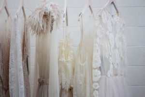 A clothing rack of white and cream sheer dresses