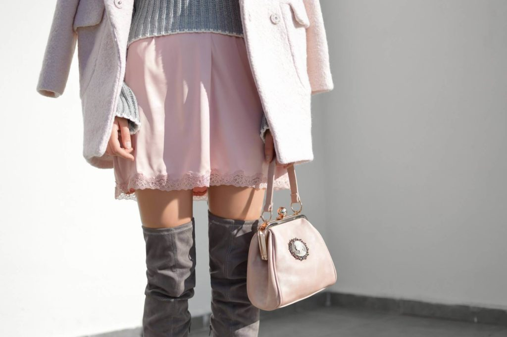 woman wears a pink coat, skirt and bag and grey jumper and over-knee boots. Stands against white wall.