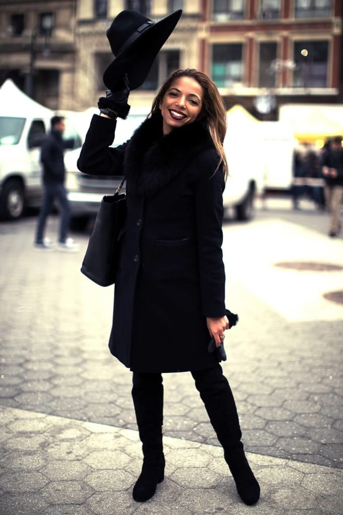 woman standing on street holding her hat in the air smiling. Black winter coat, black winter dresses, black hat.
