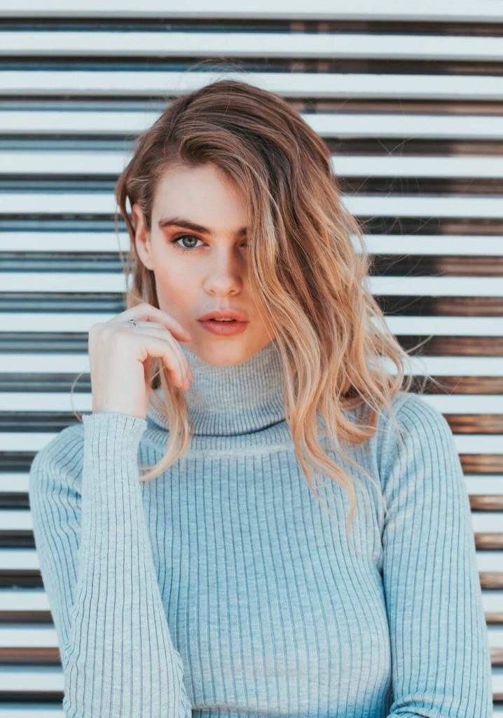 blonde woman standing against a wall wearing a grey turtle neck jumper