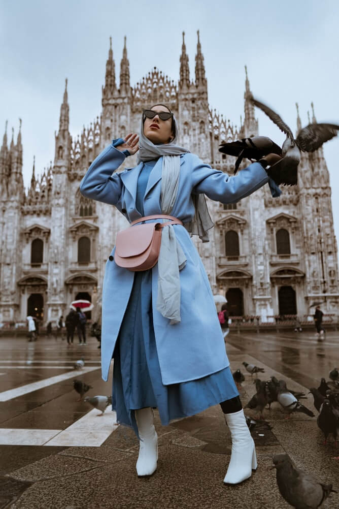 woman wearing grey headscarf, blue coat, maxi dress, pink belted bag and white boots. Poses in front of a Cathedral. Pigeons fly to one of her hands.