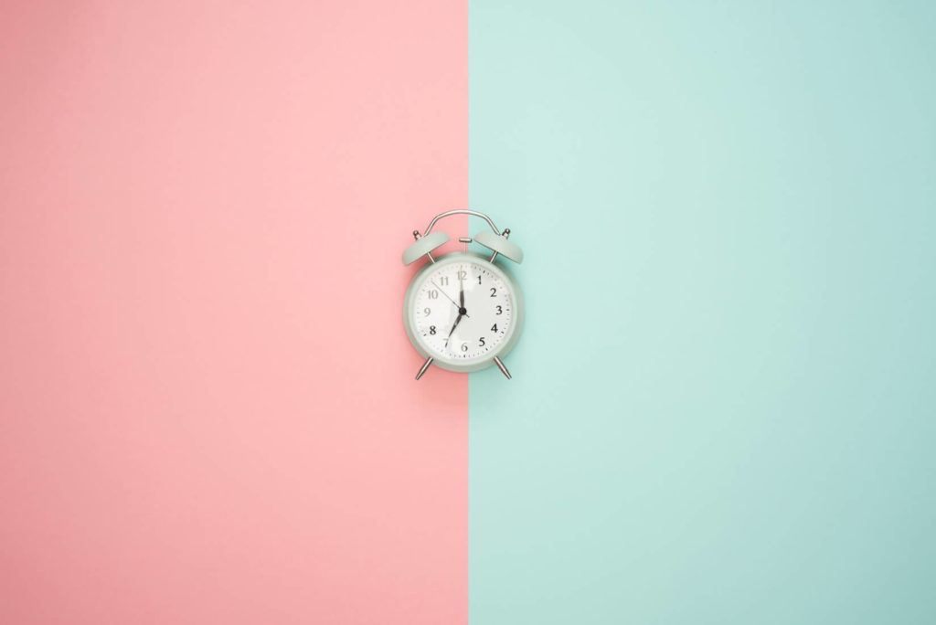 photograph of a white clock on a light pink and blue background